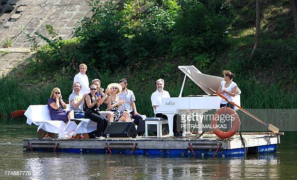 Lithuanian pianist Petras Geniusas performs on a floating pontoon on the river in Vilnius on July 29 2013 as part of the piano lt summer festival in...