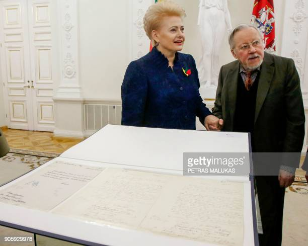 Lithuanian President Dalia Grybauskaite and Vytautas Landsbergis the first postcommunist Lithuanian president look at the historic document called...