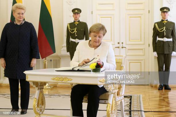 Lithuanian President Dalia Grybauskaite looks on as German Chancellor Angela Merkel signs the guest book during a meeting on September 14 2018 in...