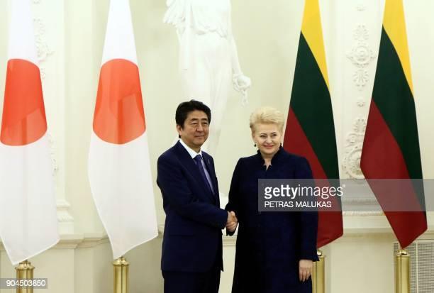 Lithuanian President Dalia Grybauskaite shake hands with Japanese Prime Minister Shinzo Abe in Vilnius on January 13 2018 / AFP PHOTO / Petras Malukas