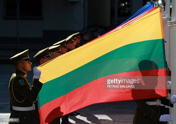 Lithuanian soldiers hold their national flag during a ceremony in front of the governmental palace in Vilnius on July 1 2013 The small Baltic nation...