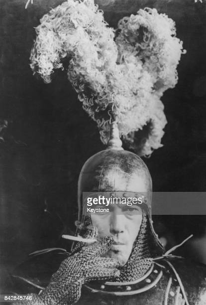 Lithuanianborn actor Laurence Harvey smokes a cigarette during a break in rehearsals for the musical 'Camelot' at the Theatre Royal Drury Lane London...