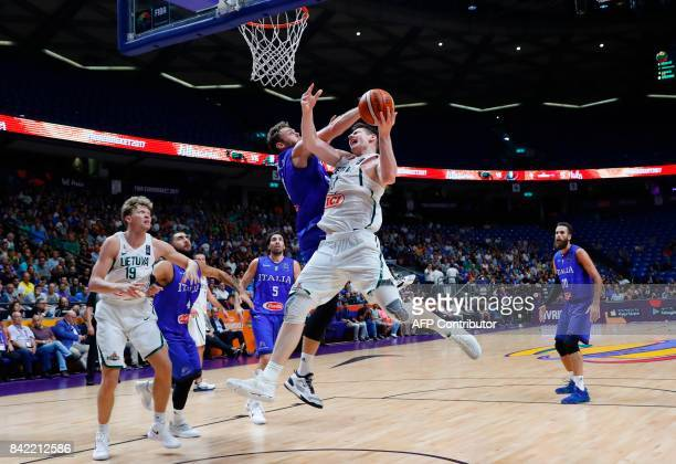 Lithuania's Arturas Gudaitis attempts a shot as he is marked by Italy's Nicolo Melli during the FIBA EuroBasket championship basketball match between...