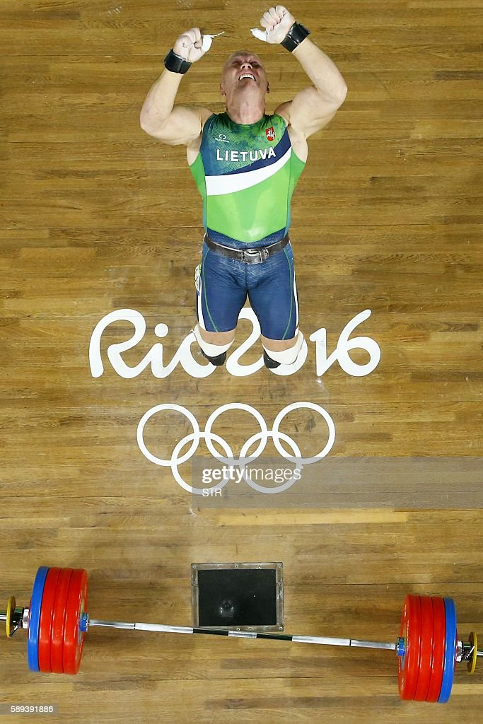 Lithuania's Aurimas Didzbalis, jumps to celebrate after winning the bronze medal of the men's weightlifting 94kg event at the Rio 2016 Olympic Games in Rio de Janeiro on August 13, 2016. / AFP / POOL / STR
