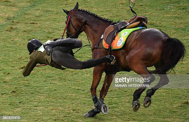 Lithuania's Justinas Kinderis is thrown from his horse in the show jumping portion of the men's modern pentathlon event at the Deodoro Stadium during...