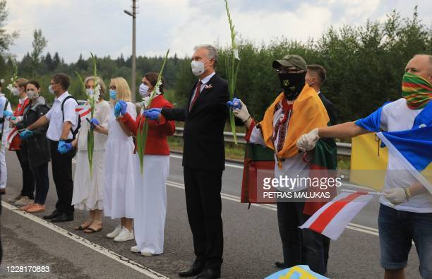 Lithuania's President Gitanas Nauseda forms a human chain with other people from Vilnius to Medininkai along the border with Belarus to show...