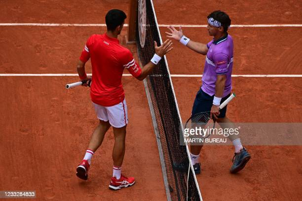 Lithuania's Ricardas Berankis and Serbia's Novak Djokovic shake hands at the end of their men's singles third round tennis match on Day 7 of The...