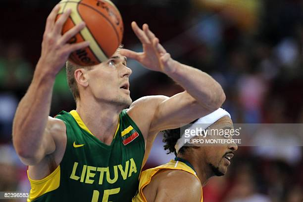 Lithuania's Robertas Javtokas jumps for the basket blocked by Australia's CJBruton during the men preliminary round group A basketball match of the...