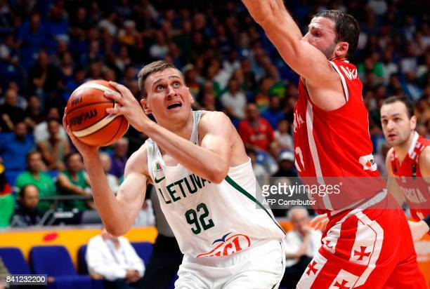 Lithuania's shooting guard Edgaras Ulanovas fakes a shot as he is marked by Georgia's shooting guard Manuchar Markoishvili during the FIBA EuroBasket...
