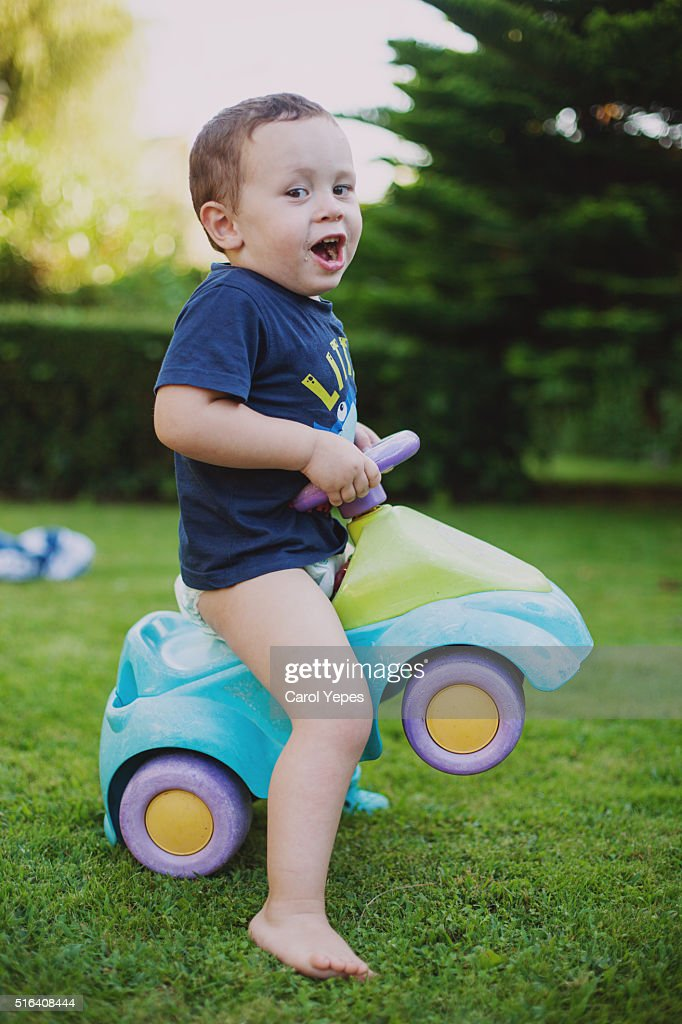 litle boy playing in yard with car : Stock Photo