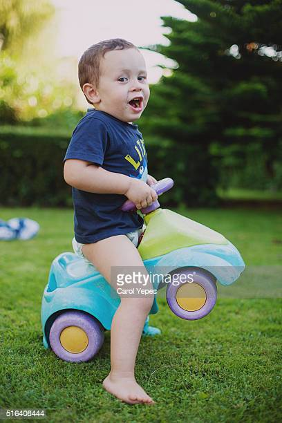 litle boy playing in yard with car - diaper boy stock photos and pictures