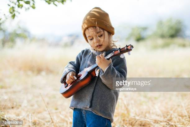 litlle girl playing guitar - playing stock pictures, royalty-free photos & images