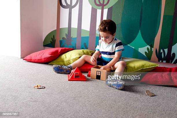 Litlle kid playing with wooden toys on floor