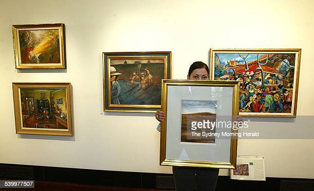 Litsa Veldekis art specialist at the Deutscher Menzies auction rooms holding Sidney Nolan's Kelly with Rifle surrounded by [left top] Arthur Boyd's...