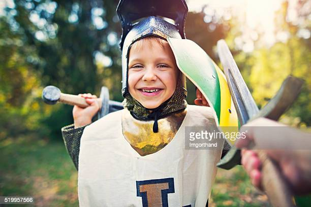 Litte boy playing knight and having fun fighting