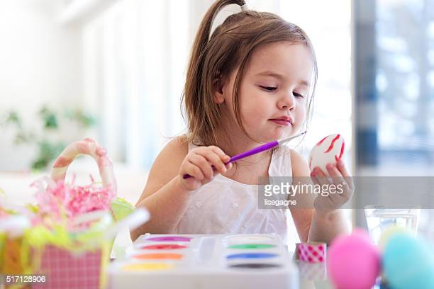 Litte girl painting easter eggs