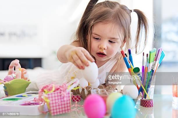Litte girl painting easter eggs