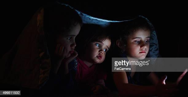 Litte Kids Watching a Movie Under a Blanket
