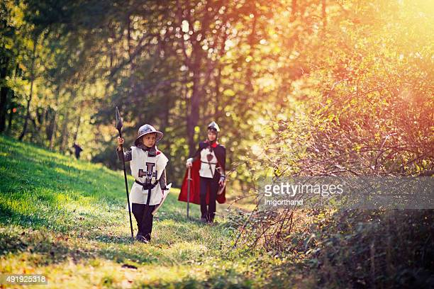 Litte knight and his squire walking in forest