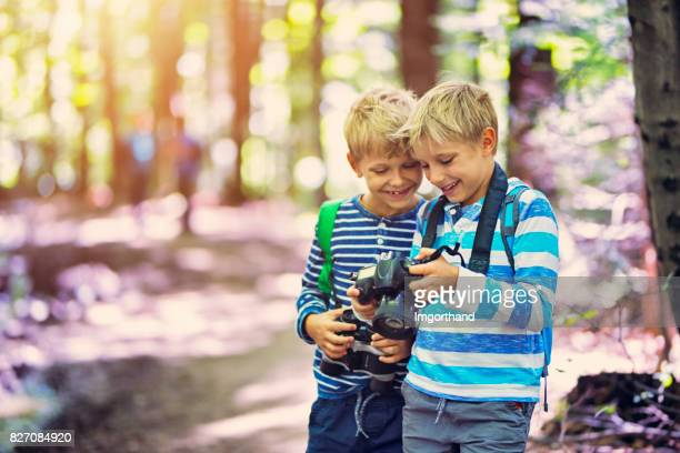 Littel boys photographing in forest