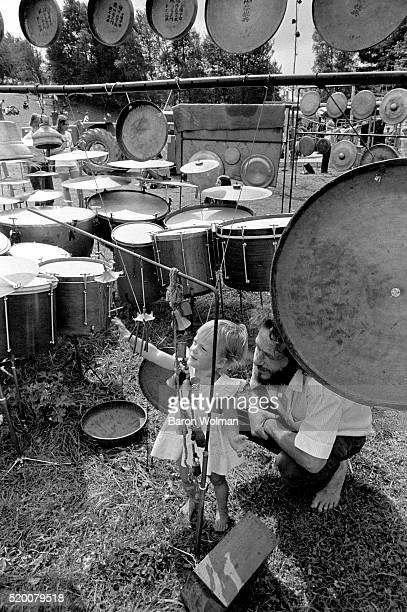 A littel girl plays with a wind chime surrounded by drums and gongs at the Woodstock Music Art Fair Bethel NY August 15 1969