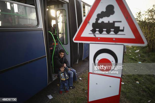 Littel syrian boy waves as migrants wait on a bus before being taken by police to board a train to the austrian border on September 15, 2015 in...