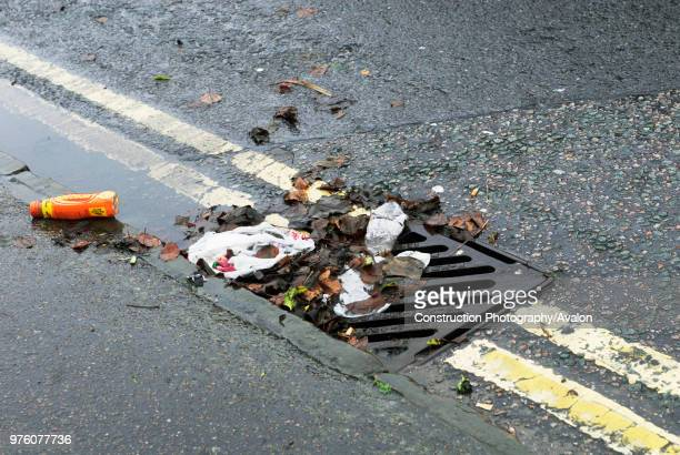 Litter, leaves and puddle in gutter by drain.