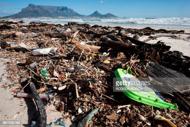 Litter mostly plastic lies on a beach close to the city centre tangled up with kelp with Table Mountain in the background on June 3 in Cape Town On...