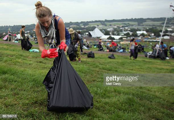 A litter picker one of the 600 who were signed on to start today picks up some rubbish on the start of the big clear up of the Glastonbury Festival...