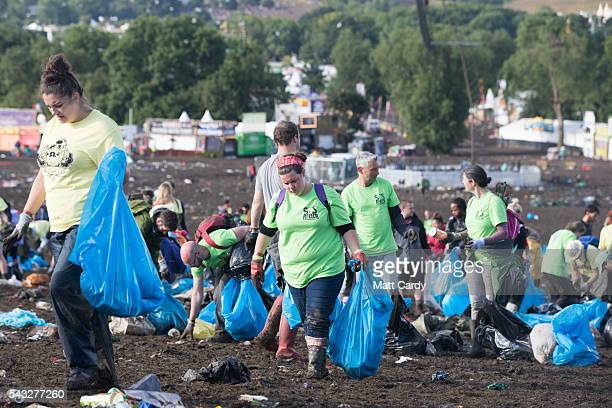 Litter pickers begin the job of clearing the fields in front of the main Pyramid Stage at the Glastonbury Festival 2016 at Worthy Farm Pilton on June...