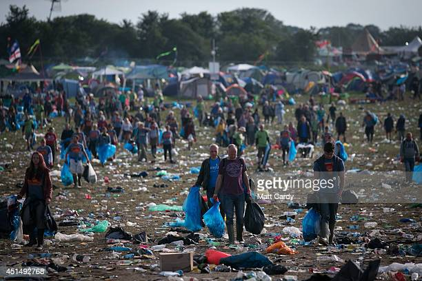 Litter pickers clear the rubbish left in front of the main Pyramid Stage at Worthy Farm in Pilton on June 30 2014 near Glastonbury England Festival...