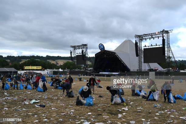 Litter pickers remove rubbish at Glastonbury Festival of Music and Performing Arts on Worthy Farm near the village of Pilton in Somerset South West...