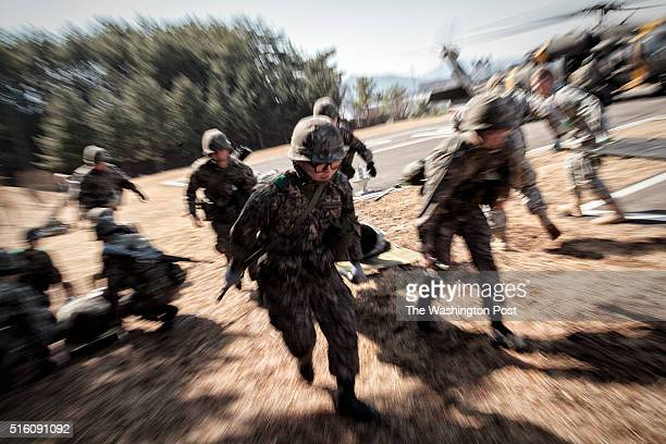 A litter team of South Korean Army rushes to a triage station carrying 'wounded' soldier from a Black Hawk during the wounded soldiers evacuation...