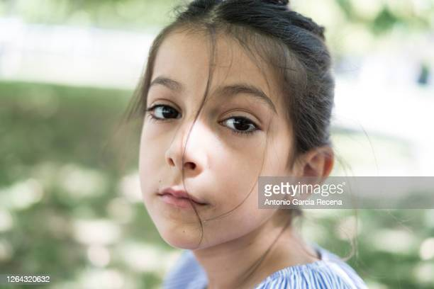 little 7 years old girl portrait in park looking at camera - black eye stock pictures, royalty-free photos & images