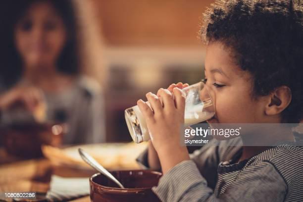 menino americano africano bebendo leite fresco de vidro. - beber - fotografias e filmes do acervo