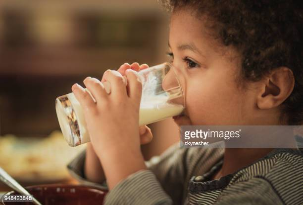 little african american boy drinking fresh milk from a glass. - milk stock pictures, royalty-free photos & images