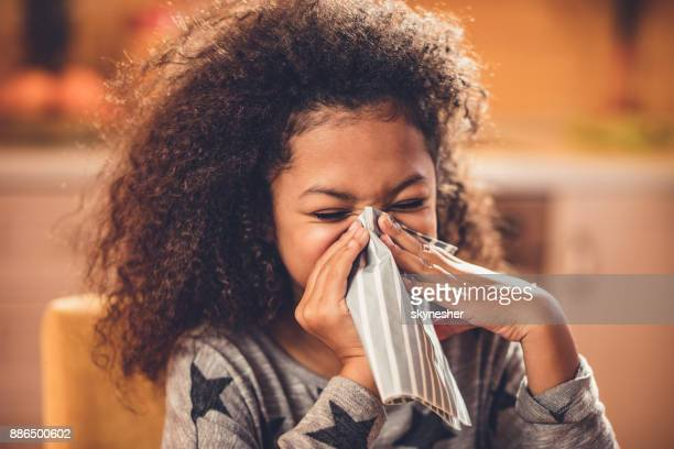Little African American girl blowing nose with a napkin.
