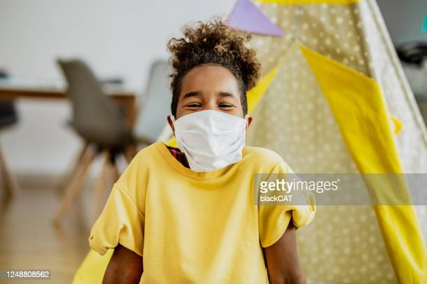 little african american girl smiling with face mask indoors - cat face mask stock pictures, royalty-free photos & images