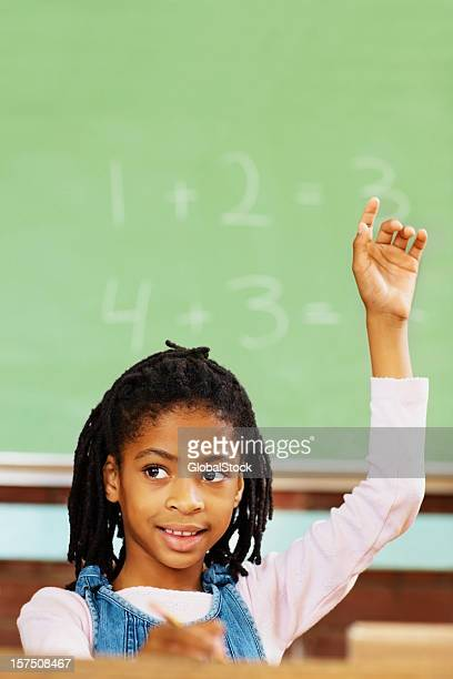 Little African American girl with her hand raised