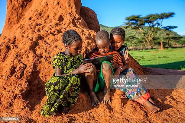 Little African children using digital tablet, East Africa