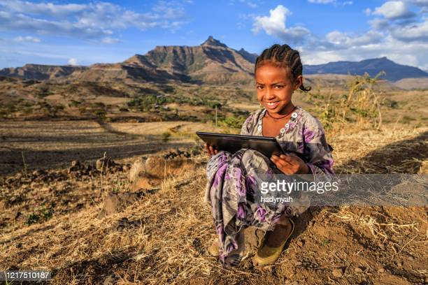 little african girl is using digital tablet, east africa - east africa stock pictures, royalty-free photos & images