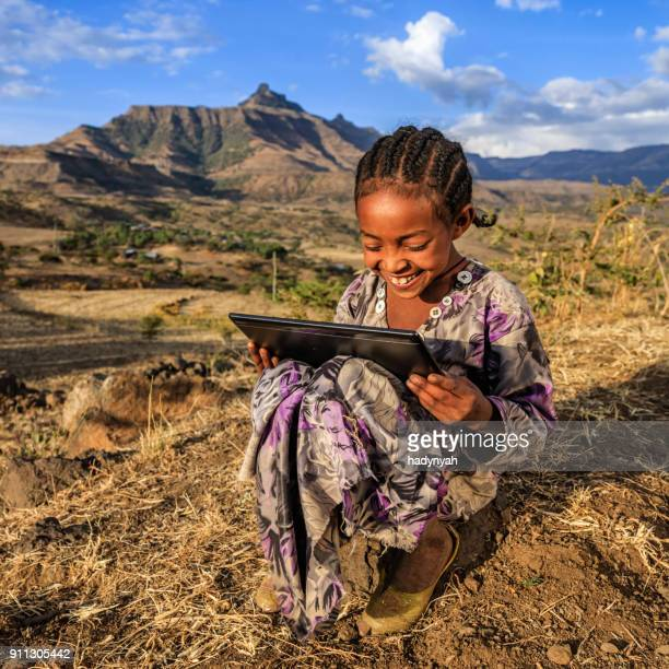 Little African girl is using digital tablet, East Africa