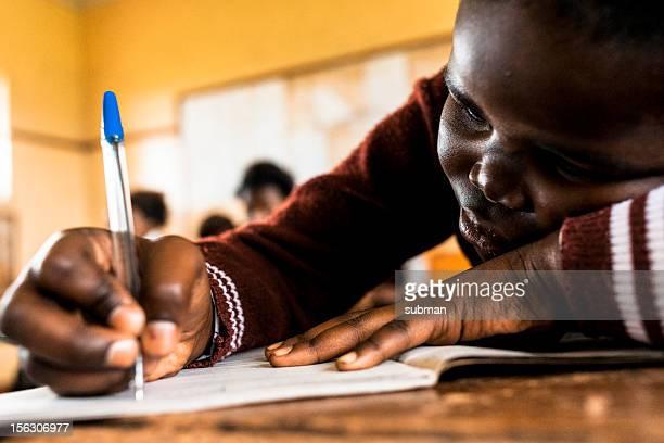 Kleine Afrikanische Mädchen Schreiben in parlamentarische Bestuhlung