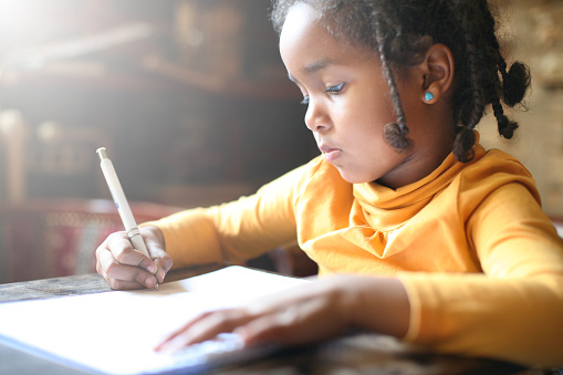 Little African girl writing. 623911912