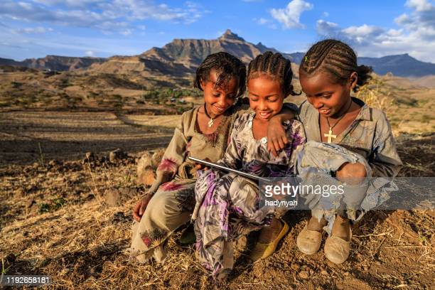 little african girls using digital tablet, east africa - east africa stock pictures, royalty-free photos & images