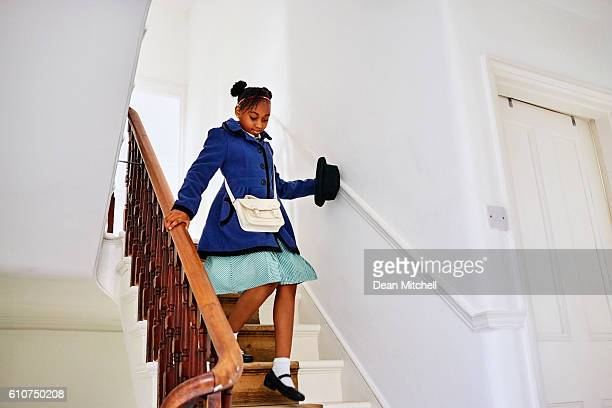 Little african school girl walking down the stairs at home