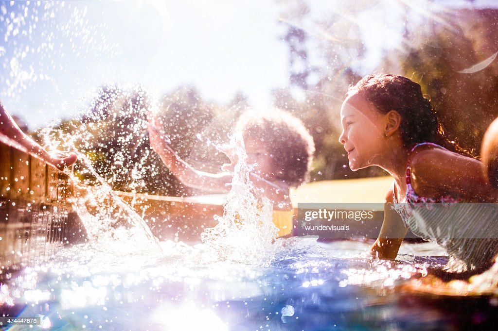 Little Afro girl and friends splashing in a pool together : Stock Photo