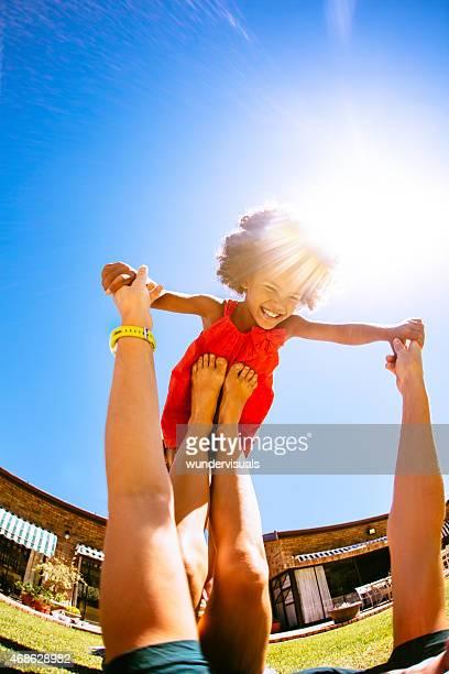 Little Afro girl on adult's feet pretending to be flying