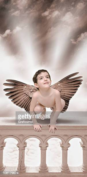Little Angel boy sitting on balustrade