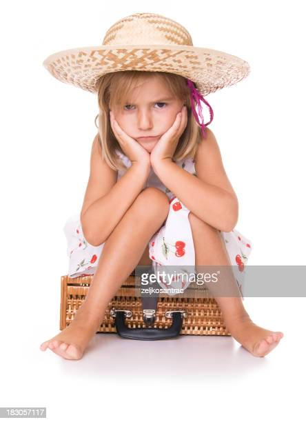 Little angry blonde girl in a hat sitting on a suitcase